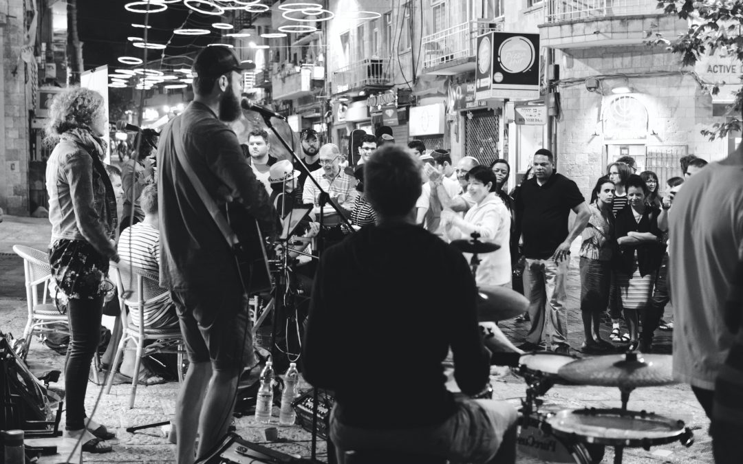 photo of a local band playing before a small crowd on a street corner